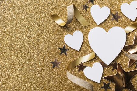 White heart shape on a golden glitter backgrond