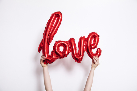 Red foil Love balloon held against a plain white background 스톡 콘텐츠 - 115749611