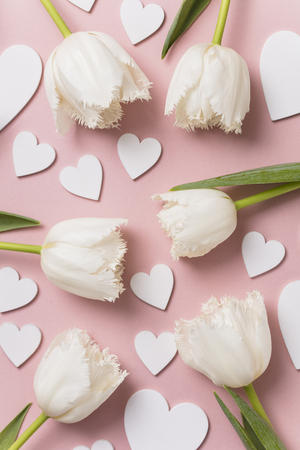White flowers and hearts on a pastel pink background 免版税图像