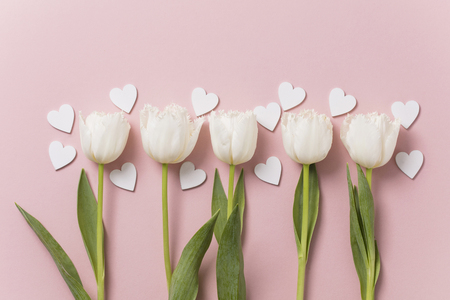 White flowers and hearts on a pastel pink background Imagens