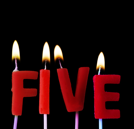 Five spell out in red birthday candles against a black background Reklamní fotografie