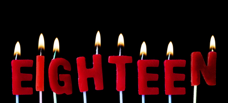 Eighteen spell out in red birthday candles against a black background Reklamní fotografie