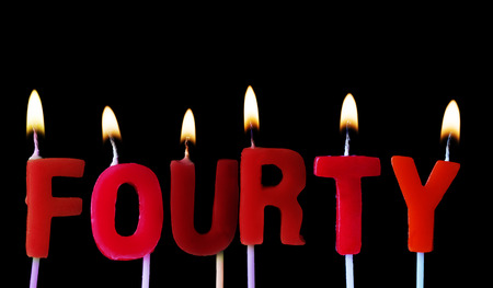 Fourty spell out in red birthday candles against a black background