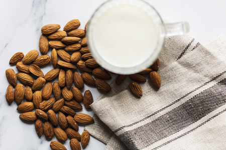 Almond milk in a glass surrounded by organic almonds Standard-Bild - 116287519