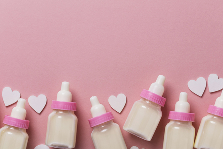 Baby bottle on a pastel pink background. New baby arrival Фото со стока