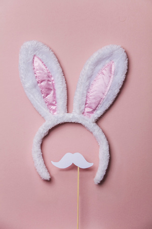 Easter bunny ears with white moustache on a pastel pink background 스톡 콘텐츠