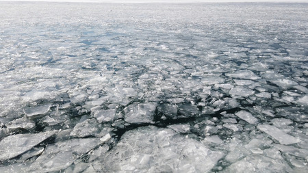 Arctic ice melting and cracking on the surface of the sea