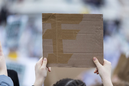 A protestor holding a blank placard at a political protest