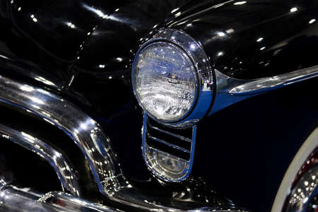 A close up of a classic vintage car headlight