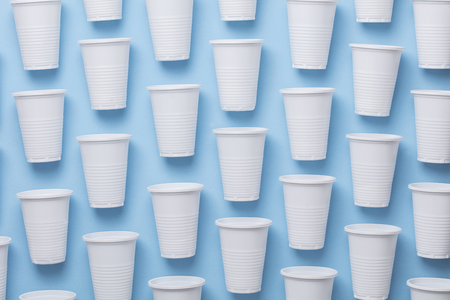Single use white plastic cups on a blue background Archivio Fotografico