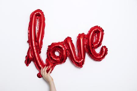 Red foil Love balloon held against a plain white background 版權商用圖片
