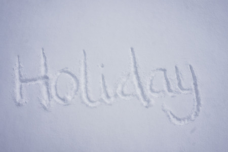 Holiday word written in a cold snow background Stock Photo