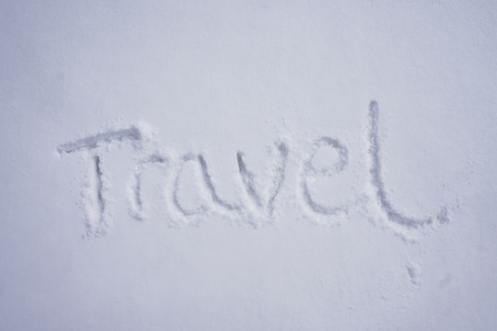 Travel word written in a cold snow background Stock Photo