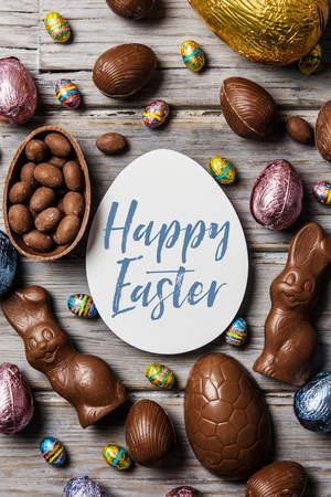 Chocolate easter eggs and bunnies on a rustic wooden background