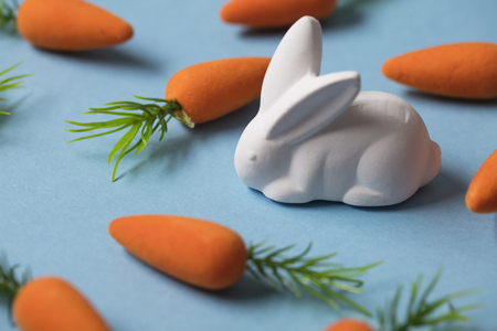 White easter bunny with orange carrots. Easter composition Banco de Imagens