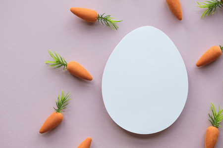 Easter composition with blank white easter egg and easter bunny carrots