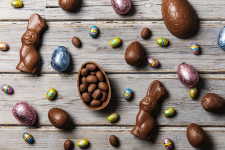 Chocolade paaseieren en konijntjes op een rustieke houten achtergrond
