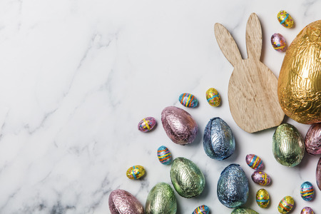 Easter bunny with foil wrapped chocolate easter eggs Stock Photo