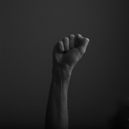 Raised clenched fist against a dark background, power, protest concept