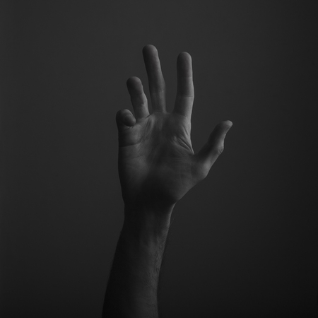 Male open hand gesture on a dark background