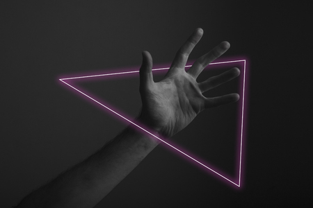 Male open hand gesture on a dark background with abstract neon light glow