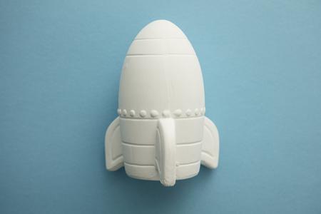 Business startup concept. Rocket ship against a blue background