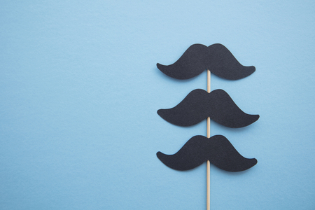 Black paper mustache on a blue background. Fathers day or mens health concept