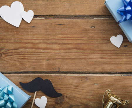 Father's day composition. Gift box with hearts and mustache on wooden background Stock Photo