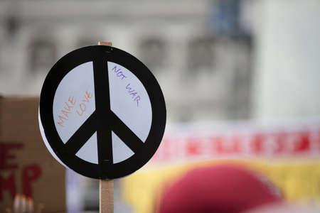 A person holds a peace sign banner at a protest Stock Photo
