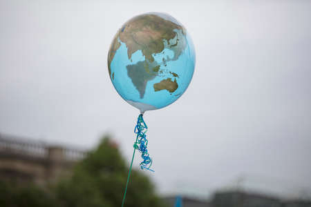 An earth shaped balloon floating on a string. Climate and environment concept