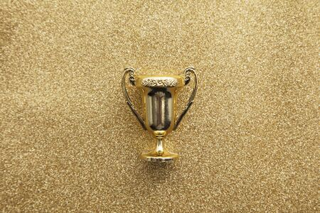 Gold winners achievement trophy on a gold glitter background Zdjęcie Seryjne