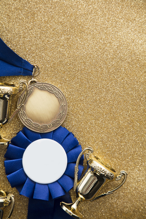 Gold winners achievement trophy on a gold glitter background Stockfoto