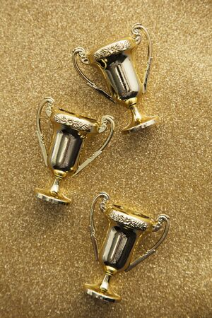 Gold winners achievement trophy on a gold glitter background Banque d'images