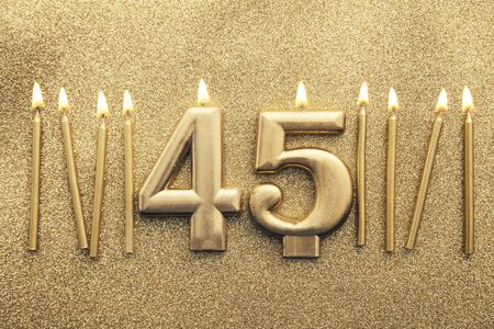 Number 45 gold celebration candle on a glitter background