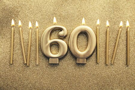 Number 60 gold celebration candle on a glitter background
