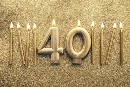 Number 40 gold celebration candle on a glitter background