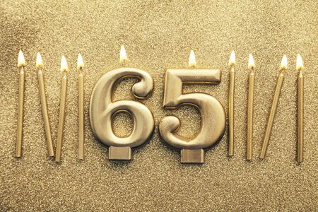 Number 65 gold celebration candle on a glitter background