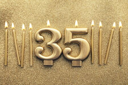 Number 35 gold celebration candle on a glitter background Imagens