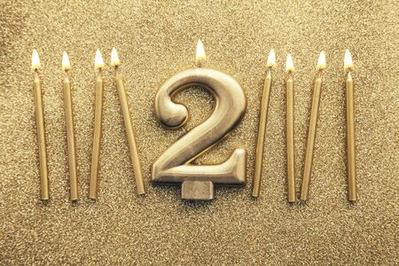 Number 2 gold celebration candle on a glitter background