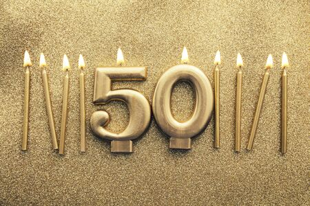 Number 50 gold celebration candle on a glitter background