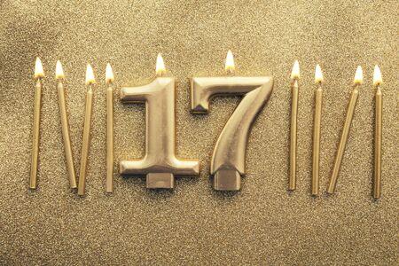 Number 17 gold celebration candle on a glitter background