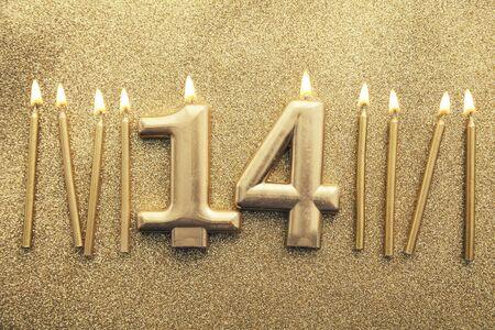 Number 14 gold celebration candle on a glitter background