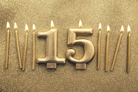 Number 15 gold celebration candle on a glitter background