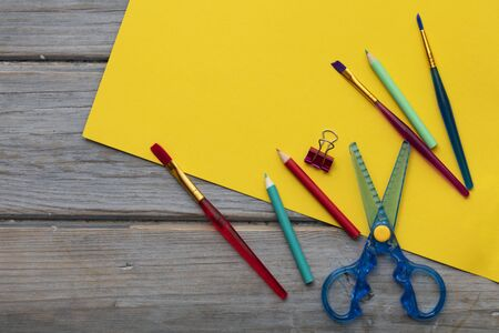 Childrens art and craft composition. Art supplies and yellow paper on a desk