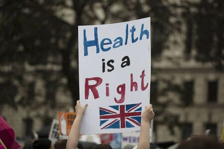 A protestor holds a political banner with health is a human right message