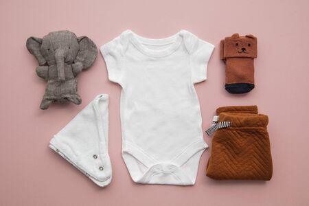 Newborn child clothing layout on a pastel pink background Stok Fotoğraf - 131352264