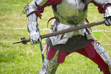 A medieval knight in amrour holding a weapon
