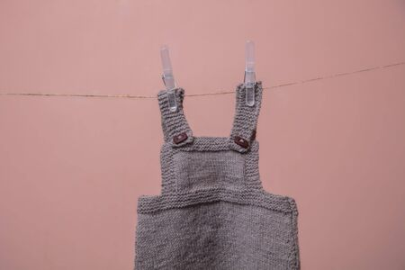 Handmade knitted baby clothes hanging on a line Stok Fotoğraf - 131352272
