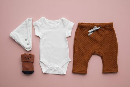 Newborn child clothing layout on a pastel pink background