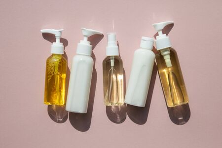 A collection of beauty cosmetic producs in clear bottles on a pink background Фото со стока